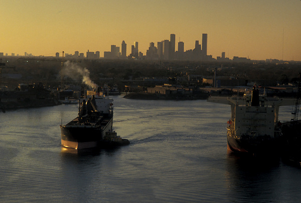 Tanker guided by a tugboat in the Port of Houston in front of the Houston skyline