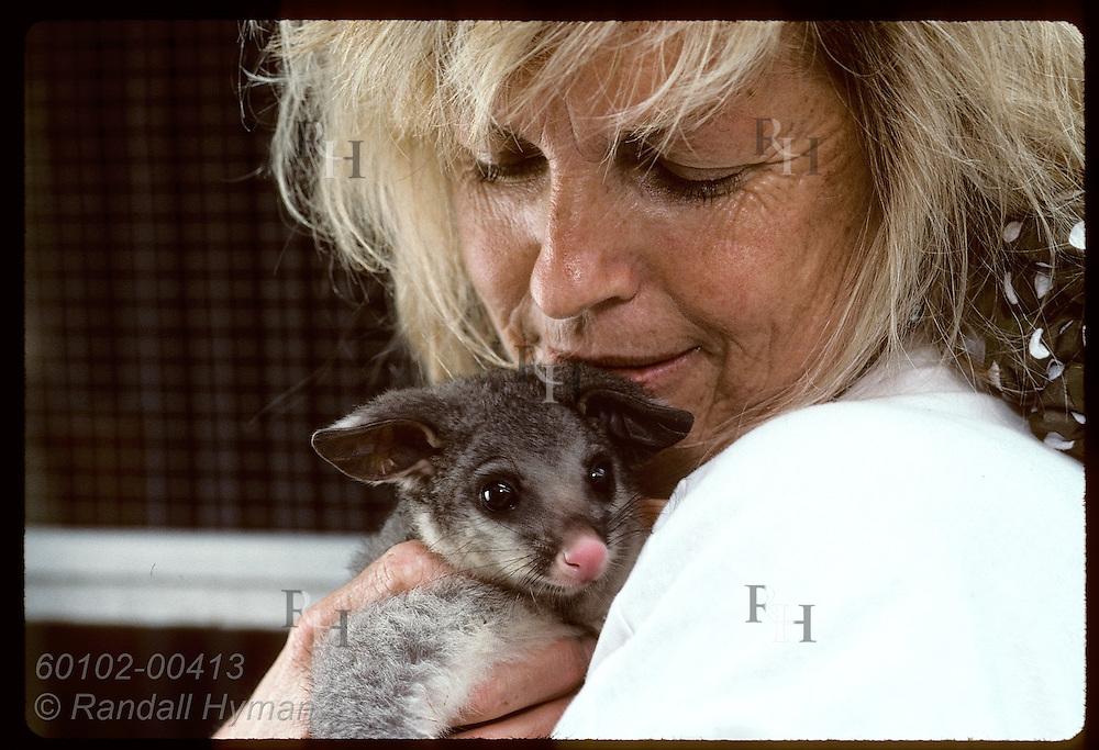 Woman hugs seven-month-old brush-tail possum at Eprapah rehab center near Brisbane. Australia