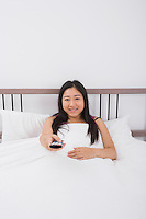 Portrait of smiling woman changing channels with remote control in bed