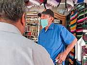 Apr. 27, 2009 -- NOGALES, SONORA, MEXICO: A vendor in the market in Nogales, Sonora, Mexico, wears a surgical mask to protect himself from the swine flu. The Mexican government broadened its efforts to control the outbreak of swine flu Monday closing schools throughout the country. In Nogales, on Mexico's northern border with the US, people started wearing masks as news of the outbreak spread.  Photo by Jack Kurtz
