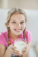 Portrait of happy young girl drinking milk