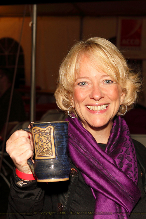 "Lite 94.5's Kim Faris holds her 2012 mug during the Preview Party for the 41st annual Oktoberfest at the Dayton Art Institute, Friday, September 21, 2012.  Note the purple scarf, ""to support World Alzheimer's Action Day."""