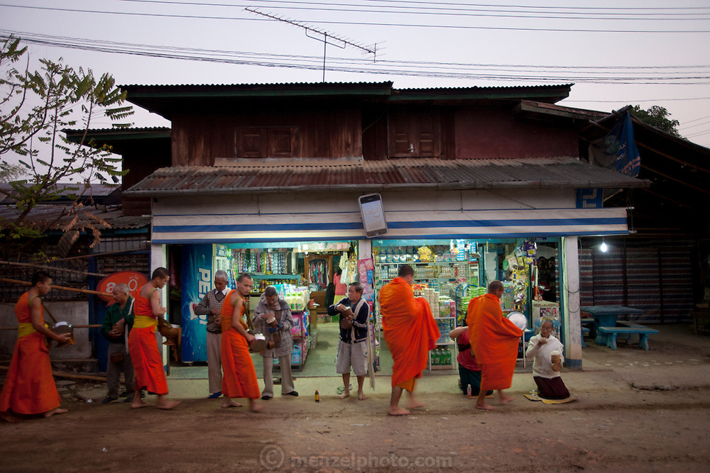 """Ban Saylom Village, just South of Luang Prabang, Laos. Every morning at dawn, barefoot Buddhist monks and novices in orange robes walk down the streets collecting food alms from devout, kneeling Buddhists. They then return to their temples (also known as """"wats"""") and eat together. This procession is called Tak Bat, or Making Merit."""