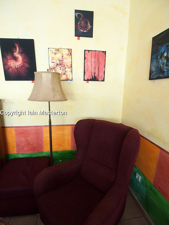 Detail armchair and paintings in bohemian cafe Tasso on Karl Marx Allee in former East Berlin Germany