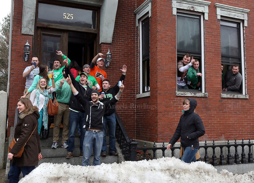 (Boston, MA - 3/15/15) People cheer from a stoop and from open windows along East Broadway during the St. Patrick's Day Parade in South Boston, Sunday, March 15, 2015. Staff photo by Angela Rowlings.