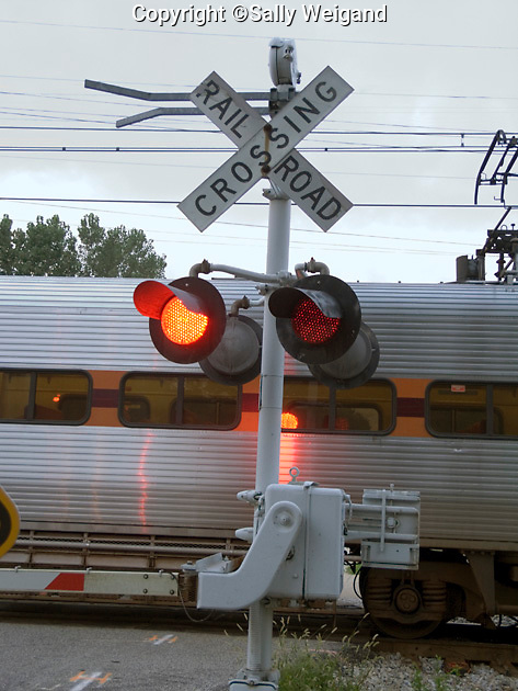 railroad crossing sign, red lights flashing, passenger train crossing road