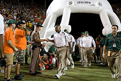 Miami head coach Randy Shannon greets a law enforcement officer as he makes his way to the field before the start of the game.  The #19 Virginia Cavaliers defeated the Miami Hurricanes 48-0 at the Orange Bowl in Miami, Florida on November 10, 2007.  The game was the final game played in the Orange Bowl.