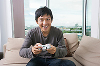 Excited mid adult man playing video game on sofa