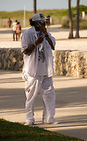 A man talks in his cellular phone on the Miami Beach Urban Weekend 2008. The Miami Beach Urban weekend in the largest Urban Festival in the World, that caters toward the Hip Hop Generation. Over 300.000 participants make the annual trek to South Beach for 4 days full of fun, food, festivities, entertainment, music, and more.
