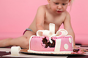young blonde girl of two sits on a checkered floor, eats a whole birthday cake.  Model release available