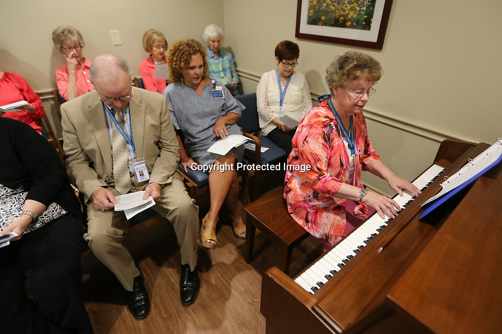 Pat Hinton, with the Pastoral Care Department at the Mississippi Medical Center, plays the piano and leads the music durng the chapel dedication ceremony and meditation room on Wednesday afternoon.