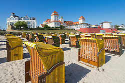 View of traditional Strandkorb chairs on beach and Kurhaus Binz Hotel at Binz seaside resort on Rugen Island in Germany