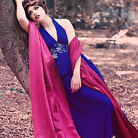 Young woman with brunette hair in blue dress and a red stole standing alone in the forest like a fairytale