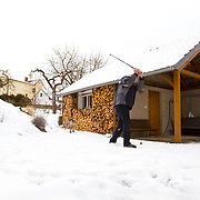 A man practices his golf swing using his dog to retrieve the ball during winter days in Tynec, Czech Republic.