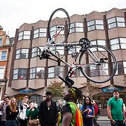Hackney carnival 2014. The procession started in Ridley Road and passed by the The Hackney Town Hall with thousands of spectators lining the road. A dancer leads the procession with a bike balancing on his head.