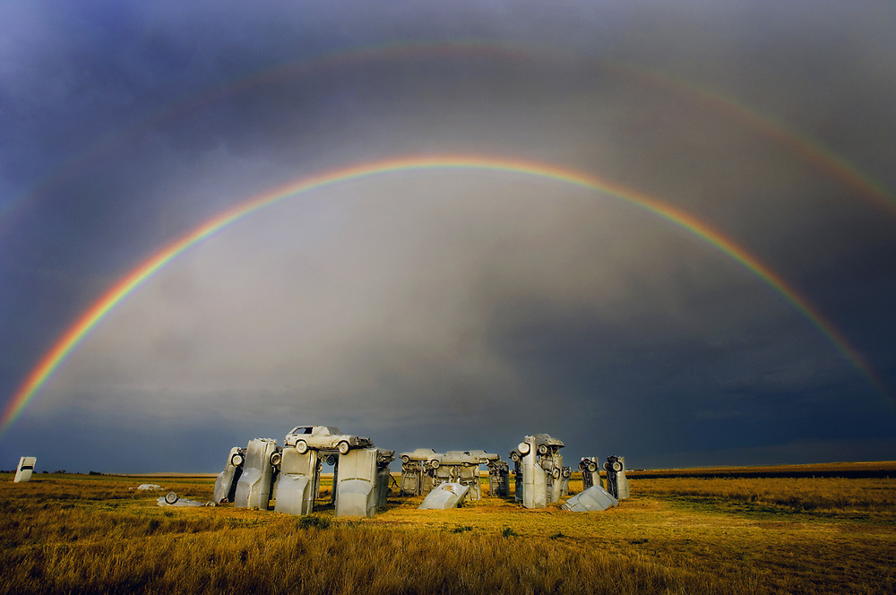 Carhenge, Nebraska raodside sculpture resembles that of the European<br /> Stonehenge scuptlure on the Great Plaiones near Alliance, Nebraska with a backdrop of passing summer thunderstorm and rainbow