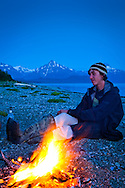 A young man relaxing by the campfire on the beach of Glacier Bay at dusk.  Glacier Bay National Park & Preserve, SE Alaska. Model Released #0152010MR