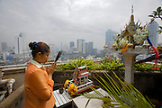 Ghost House on rooftop of Tower Inn Hotel, overlooking BTS Skytrain and skyscrapers in Silom Road area. A hotel clerk offering inscense.