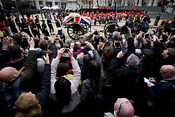 © London News Pictures.17/04/2013. London, UK.  Members of the public line the streets outside St Paul's Cathedral in London as the coffin arrives draped in the union flag for the funeral of former British Prime Minister, Margaret Thatcher on April 17, 2013. Photo credit : Ben Cawthra/LNP
