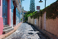 Guayaquil, Ecuador--April 15, 2018. A photo looking down a cobblestone side street of colorful houses in Guayaquil Ecuador.