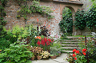 Late summer plants including penstomen, pelargonium, red persicaria, dahlia and lilium against a red brick wall, arched doorway and stone steps;  Great Dixter, East Sussex, UK<br /> August