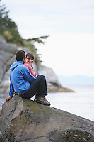 Couple sitting on rock by ocean