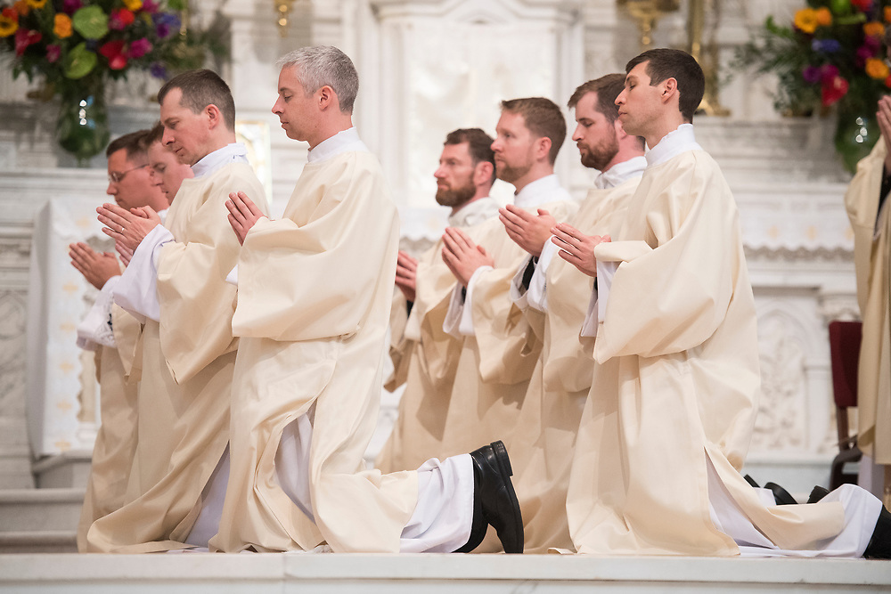DENVER, CO - MAY 13: From left, the Revs. Nicholas Larkin IV, John Mrozek II, Bogusław Rębacz, Peter Wojda, Francesco Basso, Daniel Ciucci, Daniel Eusterman and Shaun Galvin kneel for a blessing from Denver Archbishop Samuel Aquila (not pictured) during the men's ordination to the priesthood at the Cathedral Basilica of the Immaculate Conception on May 13, 2017, in Denver, Colorado. (Photo by Daniel Petty/for Denver Catholic)