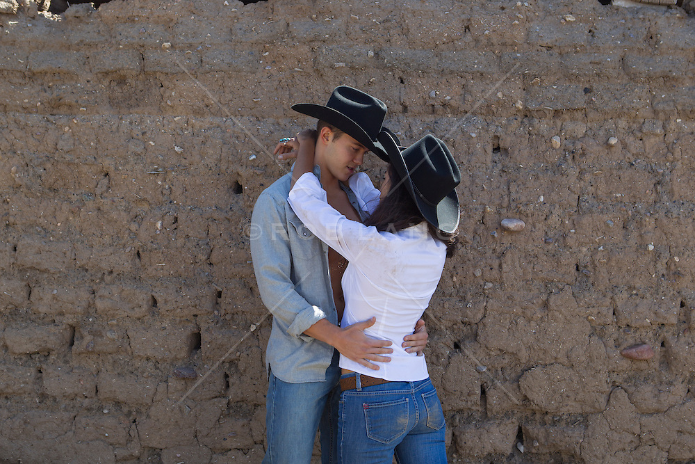 cowboy and a girl together against an adobe wall in New Mexico