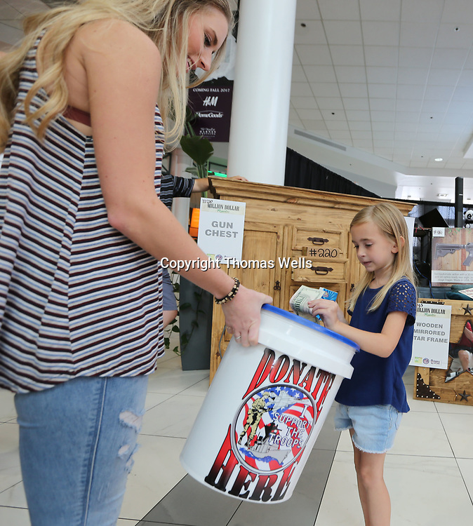 Karli Wood, left, collects a donation from Aubrey Claire Churchill, 5, as Scott Burn begins his fundraising campaign for the Purple Heart Homes organization.