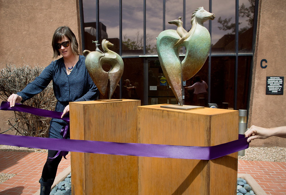 "mkb041117b/metro/Marla Brose -- Nan Masland, Bernalillo County's public art project coordinator, wraps a purple ribbon around the bronze sculpture, Bird Ryders, which was installed inside the courtyard of the Rape Crisis Center of Central New Mexico, and was dedicated Tuesday, April 11, 2017, in Albuquerque, N.M. The pieces were funded by Bernalillo County 1% for the Arts. ""My goal is that they offer hope,"" said Enrico Embroli who created the sculpture. (Marla Brose/Albuquerque Journal)"