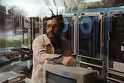 Earthquake research. Geophysicist, William Prescott in the computer data room, with earthquake data recording equipment behind him, at the U.S. Geological Survey's laboratory at Menlo Park, California. USA MODEL RELEASED.