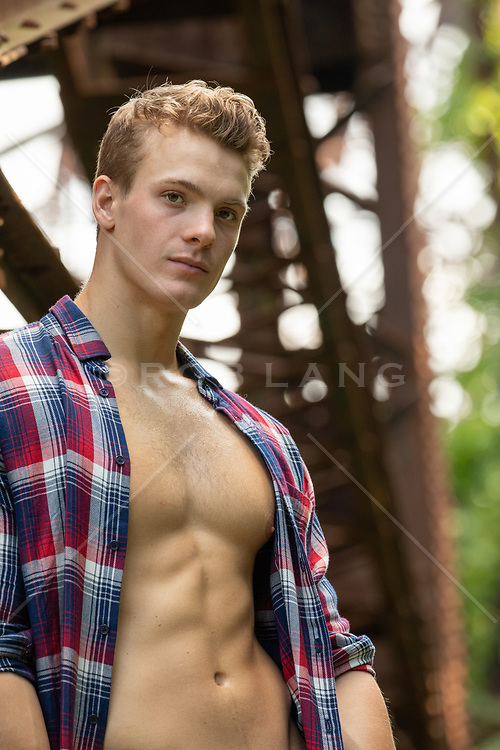All American good looking man with open shirt by rusted railroad trestle