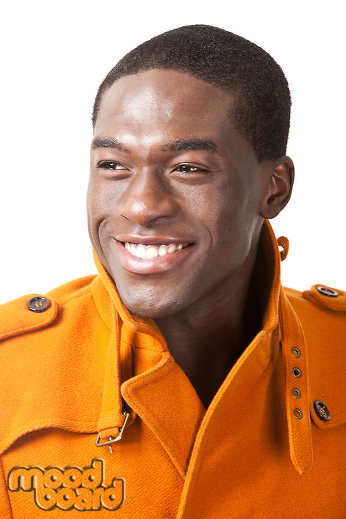 Happy young man in orange trench coat smiling against white background