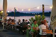 Restaurantterrasse am Wasser, Copa Cagrana - Sunken City, Donauinsel, Wien, Österreich .|.Copa Cagrana - Sunken City, Danube at dusk, Vienna, Austria..