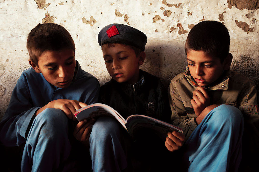 Pakistan/ Afghan refugees/ Boys read an exercise book during morning lessons at their school in the Khazana refugee camp, Peshawar. The camp was established when refugees flooded across the border from Afghanistan during the 1979 Soviet occupation. The refugee camp has a population of 2500 and during the 2010 floods that swept through Pakistan most families were affected. The majority of people rebuilt their houses after the floods with their own resources. The most vulnerable also received support from UNHCR for reconstruction. UNHCR/Sam Phelps/ November 2011.