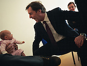 The British Rt. Hon. Alan Milburn, MP for Darlington is seen startling a young baby during a constituency visit to St George's Start-up Centre which offers crèche facilities, health and employment advice and wider support services for local children and families, in Netherfield, Nottingham England. The child looks scared to death as Milburn leans over with a fearful look on his face, as the child sits on its father's knee. Milburn was a supporter of Tony Blair (and therefore called a Blairite) and held numerous governmental posts, including: Minister of State for Health (1997-1998); Chief Secretary to the Treasury (1998-1999); Secretary of State for Health (1999-2003) and Chancellor of the Duchy of Lancaster (2004 to 2005). Source: www.alanmilburn.co.uk.