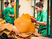 """15 DECEMBER 2014 - KLAENG, RAYONG, THAILAND: A worker sorts dried rubber sheets at a quality control station at Supark, a rubber processing plant in Klaeng, Thailand. Thailand is the second leading rubber exporter in the world. In the last two years, the price paid to rubber farmers has plunged from approximately 190 Baht per kilo (about $6.10 US) to 45 Baht per kilo (about $1.20 US). It costs about 65 Baht per kilo to produce rubber ($2.05 US). Prices have plunged 5 percent since September, when rubber was about 52Baht per kilo. Some rubber farmers have taken jobs in the construction trade or in Bangkok to provide for their families during the slump. The Thai government recently announced a """"Rubber Fund"""" to assist small farm owners but said prices won't rebound until production is cut and world demand for rubber picks up.       PHOTO BY JACK KURTZ"""