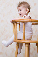 Baby boy sitting on high chair laughing
