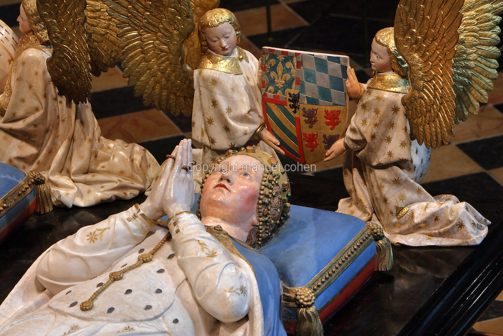 Effigy of Margaret of Bavaria with angels holding coat of arms, from the tomb of Jean sans Peur, or John the Fearless, 1371-1419, (Jean de Valois or John of Valois, Jean I, duc de Bourgogne, or John I, Duke of Burgundy) and his wife Marguerite de Baviere, or Margaret of Bavaria, 1363- 1423, 1443-70, by Jean de la Huerta, 1413-62, and Antoine le Moiturier, 1425-97, in the Grande Salle du Palais des ducs de Bourgogne, or Salle des Gardes, a 15th century Flamboyant Gothic hall, in the Musee des Beaux-Arts de Dijon, opened 1787 in the Palace of the Dukes of Burgundy in Dijon, Burgundy, France. The tomb consists of painted alabaster effigies with lions and angels, and below, figures of pleurants or weepers among Gothic tracery. The tomb was begun in 1443 (24 years after his death), by Jean de La Huerta, and Antoine le Moiturier after 1456, and finally installed in 1470. The tombs were originally from the Chartreuse de Champmol, or Chartreuse de la Sainte-Trinite de Champmol, a Carthusian monastery which was sacked in the French Revolution and the tombs moved to Dijon cathedral then here in 1827. The effigies are 19th century reconstructions, the originals being destroyed in the French Revolution. Picture by Manuel Cohen