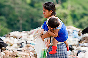 09 NOVEMBER 2004 - TAPACHULA, CHIAPAS, MEXICO: A woman and her child walk through the municipal garbage dump in Tapachula, Chiapas, Mexico. About 130 people, the poorest of the poor in Tapachula, work in the dump picking through the garbage hoping to find tidbits they can use or sell to brokers who sit on the edge of the dump and resell the garbage. Most of the dump workers are Guatemalan migrants who crossed the border hoping, at one time, to get to the United States. Now they have settled for an existence on the very edge of Mexican society. PHOTO BY JACK KURTZ