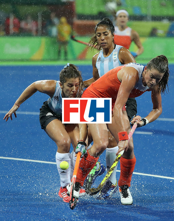 RIO DE JANEIRO, BRAZIL - AUGUST 15:  Lidewij Welten #12 of Netherlands plays the ball ahead of Julia Gomes #29 of Argentina during the quarter final hockey game on Day 10 of the Rio 2016 Olympic Games at the Olympic Hockey Centre on August 15, 2016 in Rio de Janeiro, Brazil.  (Photo by Christian Petersen/Getty Images)
