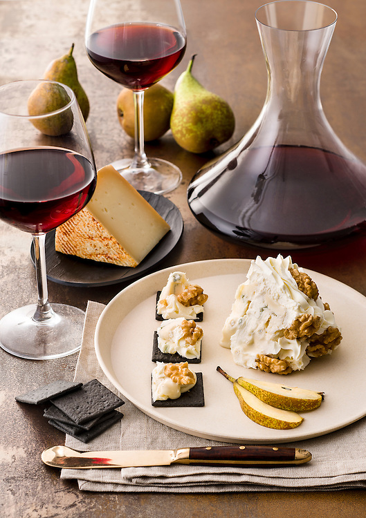 gorgonzola, mascarpone and nuts cake with pears slices and some cheese on black crackers and two glasses of red wine and red wine in a decanter bottle