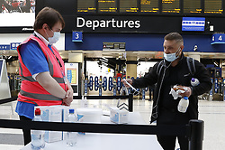 © Licensed to London News Pictures. 15/06/2020. London, UK. Passengers are given face masks as they arrive at Waterloo Station. New rules allowing some non-essential retail businneses to open and mandatory face masks on public transport have started today. Photo credit: Peter Macdiarmid/LNP