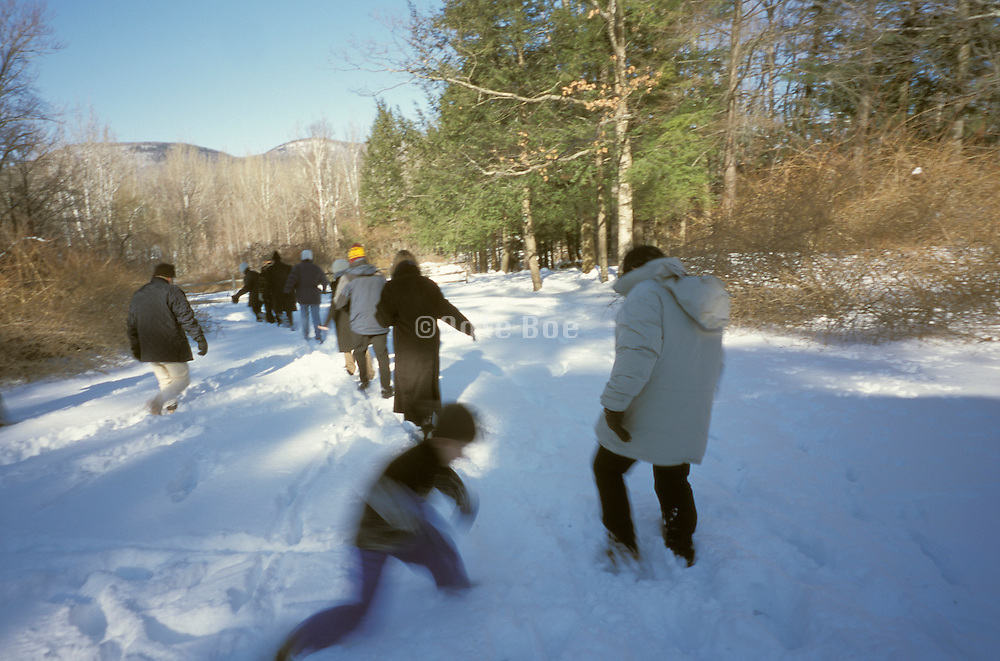 Group of people walking on a path through the snow