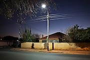A street light shines over 9th Avenue at dusk, Sydenham, Johannesburg. South Africa.