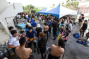ANA InterContinental Manza Beach Resort staff participating in the Team Tyura Sango coral restoration project convene a meeting with volunteers outside the dive shop at the hotel in Onna Village, Okinawa Prefecture, Japan, on Saturday, June 23, 2012. Photographer: Robert Gilhooly