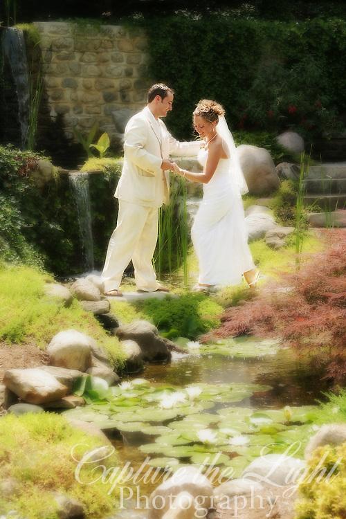 Groom helping bride across the water.