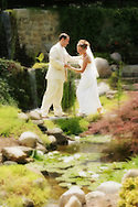 Groom helping bride across the water.