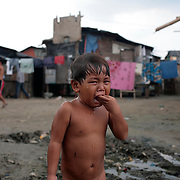 A young boy cries in the Baseco area of Tondo, one of the worst slum areas on Manila on October 9, 2008 in Manila, the Philippines. Photo Tim Clayton