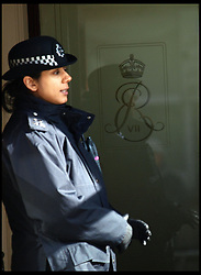 A police officer is reflected in the Royal insignia on the door at the entrance of the King Edward VII hospital in central London where the Queen is in observation Monday March 4, 2013. Photo by Max Nash / i-Images.